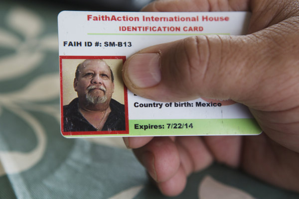 Image: Raul Garcia holds his FaithAction ID card