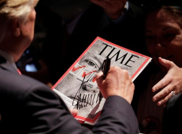 Candidate Donald Trump signs a magazine with his picture on it at a campaign rally in Raleigh, North Carolina, July 2016.      REUTERS/Joshua Roberts