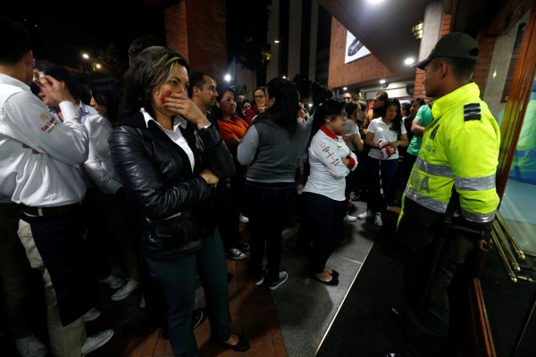 Image: People stand outside the Andino shopping center after an explosive device detonated in a restroom, in Bogota