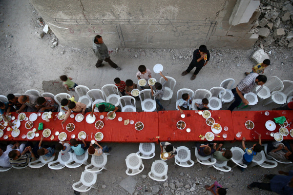 Image: People break their fast amidst damaged buildings during an Iftar in the rebel held besieged Douma neighbourhood of Damascus