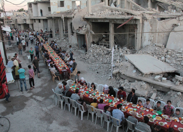Image: Residents of the rebel-held town of Douma break their fast