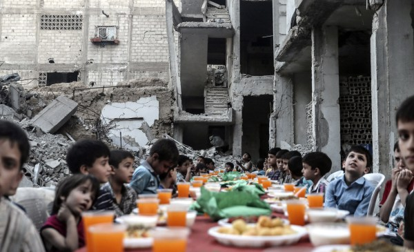 Image: Children sit at a table as they wait the evening meal at the end of daily Ramadan fast at sunset
