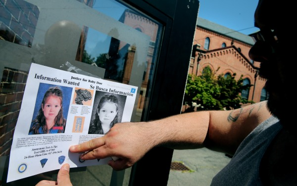 Image: A volunteer posts a flier looking to help identify Baby Doe