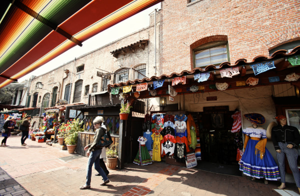 Image: Tourists shop at Olvera Street stores at El Pueblo de Los Angeles Historic  District in Los Angeles.