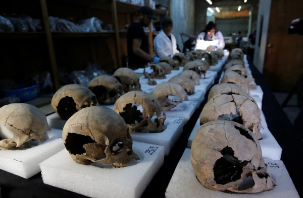 Image: Biological anthropologists from the National Institute of Anthropology and History (INAH) examine skulls discovered at a site near Templo Mayor