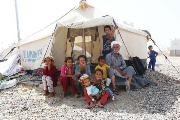Image: Saleh Saleh sits with his family outside a tent at the Hammam al-Alil refugee camp in northern Iraq