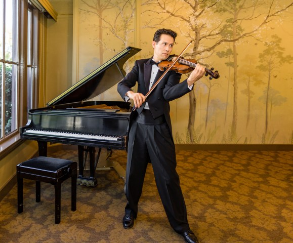 Image: Dr. Adam Kendall playing the violin in front of a piano.