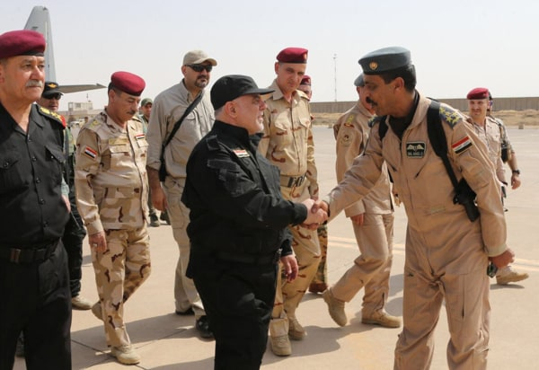 Image: Iraqi Prime Minister Haider al-Abadi, center, shakes hands with army officers upon his arrival in Mosul
