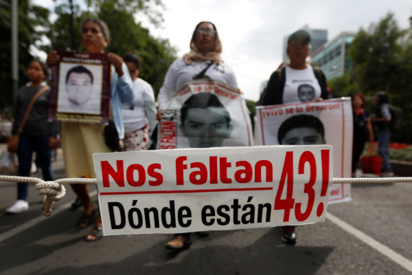 Image: A banner is seen as relatives hold posters with images of some of the 43 missing Ayotzinapa College Raul Isidro Burgos students during a march to mark the 33rd month since their disappearance, in the state of Guerrero, in Mexico City