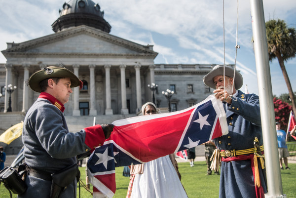 Image: Two men raise a Confederate battle flag on the South Carolina Statehouse grounds