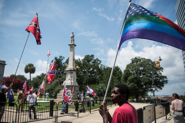 Image: Nathaniel Simmons holds a rainbow colored American flag as demonstrators fly Confederate flags