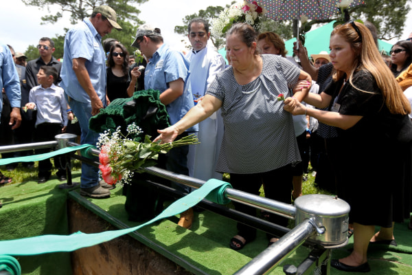 Maria Flores tosses flowers into the grave of her son Josue Flores