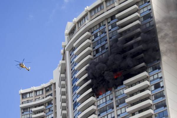 Image: A Honolulu Fire Department helicopter flies near a fire burning on a floor at the Marco Polo apartment complex
