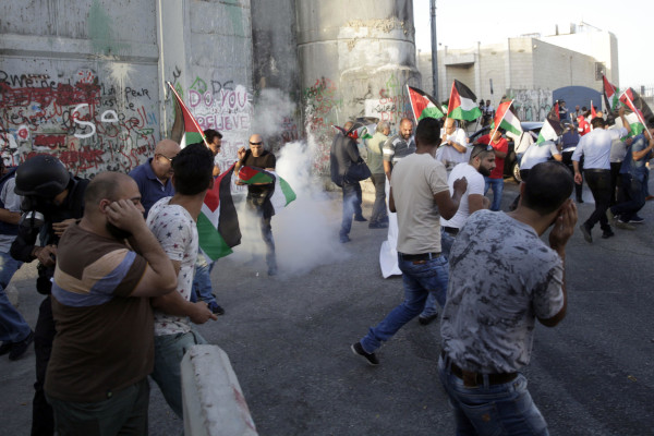 Image: Palestinians run away from stun grenades thrown by Israeli border police officers during a protest against the metal detectors at Al Aqsa Mosque