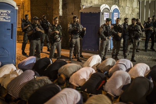Image: Thousands of Palestinian Muslims pray outside the entrance to the old city of Jerusalem