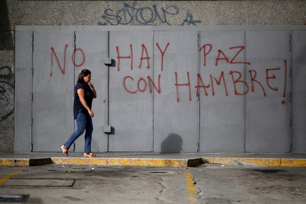 "Image: A woman walks in front of a graffiti that reads ""There is no peace with hunger"" during a strike called to protest against Venezuelan President Nicolas Maduro's government in Caracas"