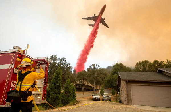 Image: An air tanker drops fire retardant on flames as firefighters continue to battle against the Detwiler fire in Mariposa, California on July 19, 2017.