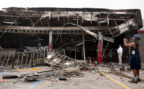 Image: People look at the burned QuikTrip gas station