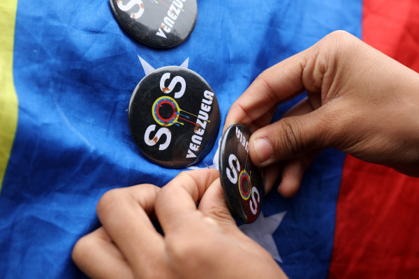 Image: A demonstrator places a badge on a Venezuelan flag at a protest  against Venezuela's President Nicolas Maduro's government during a meeting of foreign affairs ministers and representatives from across the Americas to discuss issues related to the V