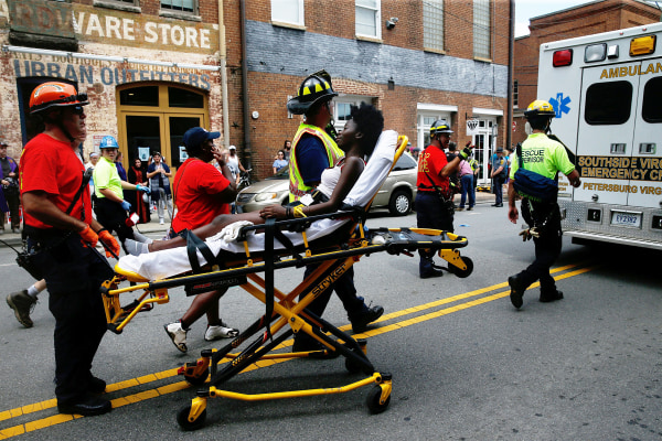 """Image: Rescue workers transport a victim who was injured when a car drove through a group of counter protestors at the """"Unite the Right"""" rally Charlottesville"""