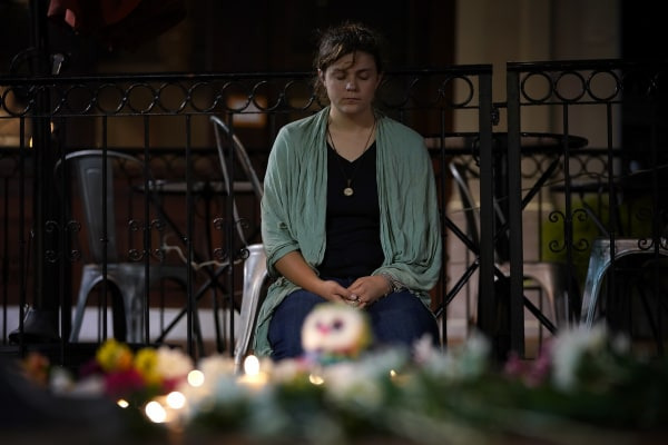 Image: A young woman sits near a makeshift candlelight vigil
