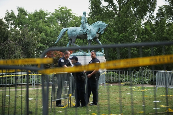 Image:  Police stand watch near the statue of Confederate Gen. Robert E. Lee in the center of Emancipation Park
