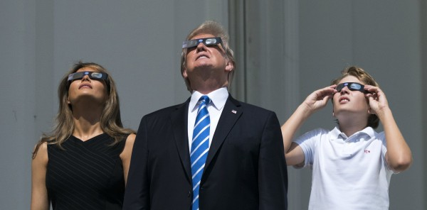 Image: President Donald Trump, First Lady Melania Trump, and Barron Trump view the solar eclipse from a balcony of the White House in Washington, DC, Aug. 21, 2017.
