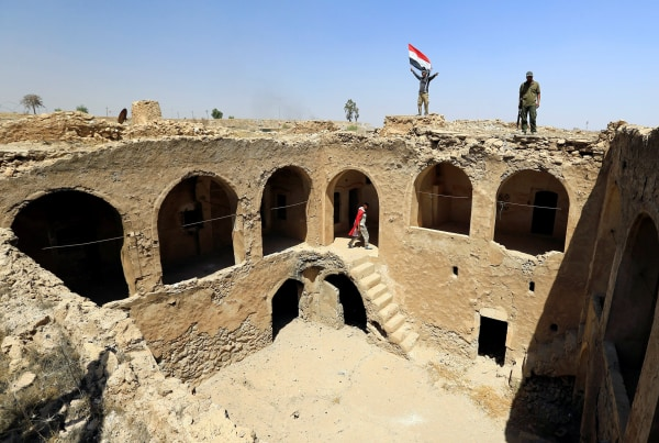 Image: Shiite Popular Mobilization Forces (PMF) members carry an Iraqi flag on the top of Tal Afar castle after it was liberated from Islamic State militants
