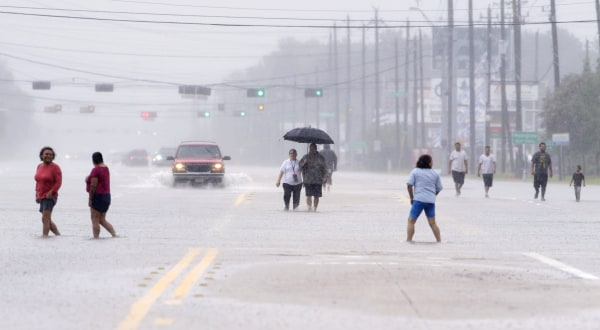 Image: Residents walk along a flooded road as they evacuate neighborhoods in Houston