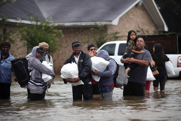 Image: People walk down a flooded street as they evacuate their homes in Houston