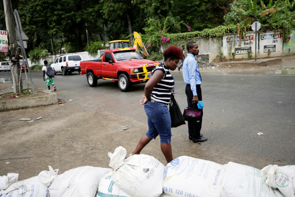 Image: A woman walks past sandbags set in a street of Cap Haitien