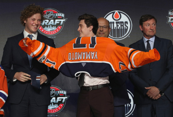 Image: Kailer Yamamoto puts on his jersey after being selected 22nd overall by the Edmonton Oilers during the NHL draft