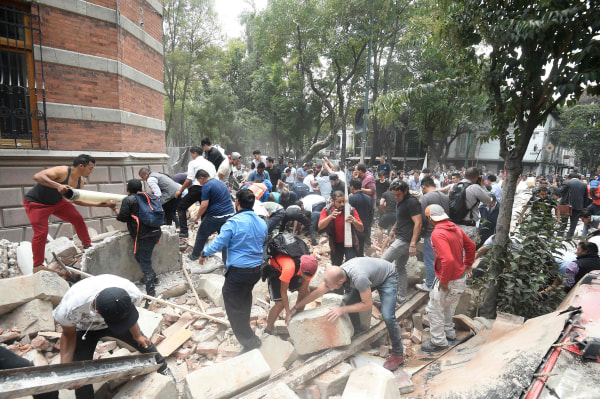 Image: People remove debris of a damaged building after a real quake rattled Mexico City
