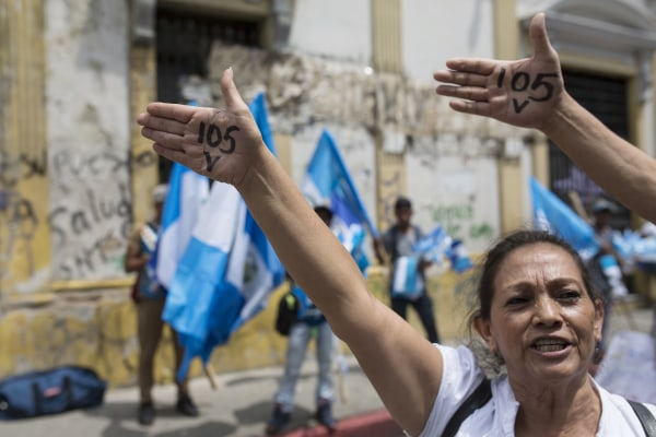 """Image: Protesters show their hands with a number """"105"""" in reference to the votes needed in Congress to lift President Jimmy Morales' immunity"""