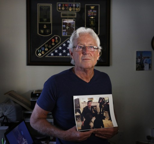 "Image: William Owens holds a photo of his youngest son Navy SEAL William ""Ryan"" Owens in Lauderdale by the Sea, Florida."