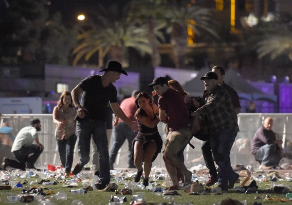 Image: People carry a wounded person at the scene of a mass shooting in Las Vegas
