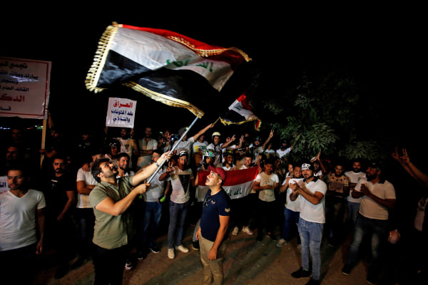 Image: Iraqi people celebrate after Kirkuk was seized by Iraqi forces as they gather on the street of Baghdad