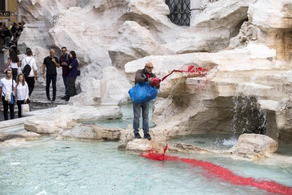Image: Graziano Cecchini pours red paint in the water of the Trevi Fountain, in Rome
