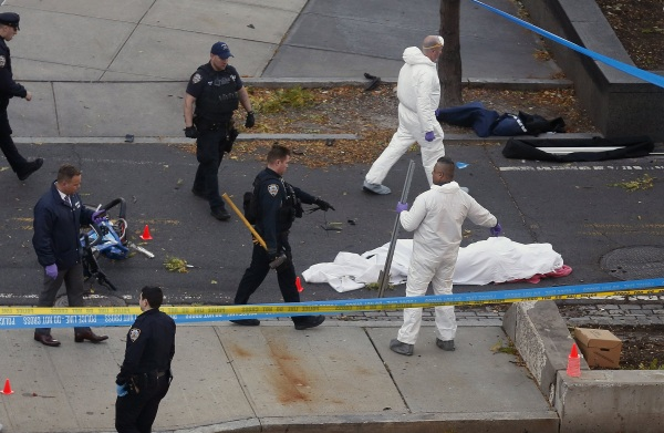 Image: Authorities investigate the scene near a covered body on a bike path after a motorist drove onto the path near the World Trade Center memorial
