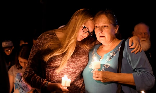 Image: Local residents embrace during a candlelight vigil for victims of a mass shooting in a church in Sutherland Springs, Texas