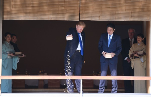 Image: Trump pours out the remaining fish food from a container as he feeds carp at a koi pond