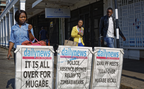 Image: Pedestrians walk past a newspaper stand in Harare, Zimbabwe