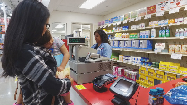 Image: Desiree Bercilla speaks to a Costco pharmacist.