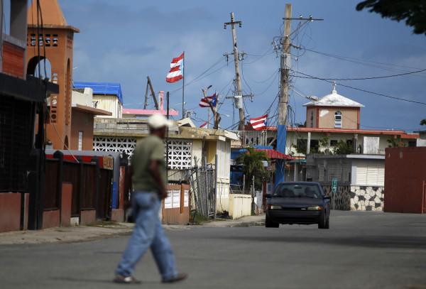 Image: A man crosses a street in the Punta Santiago beachfront neighborhood of Humacao