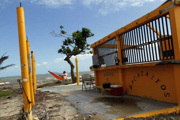 Image: A man rests in a hammock in the Punta Santiago beachfront neighborhood of Humacao