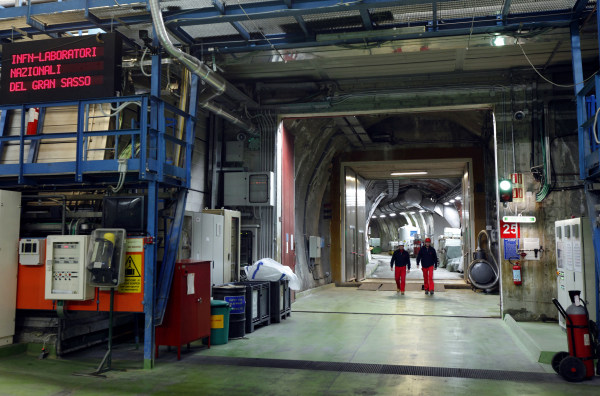 Two researchers walk down the long corridor in a nuclear physics laboratory