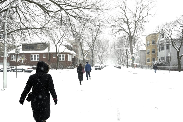 Image: People walk on snow covered streets in the Lakeview neighborhood of Chicago