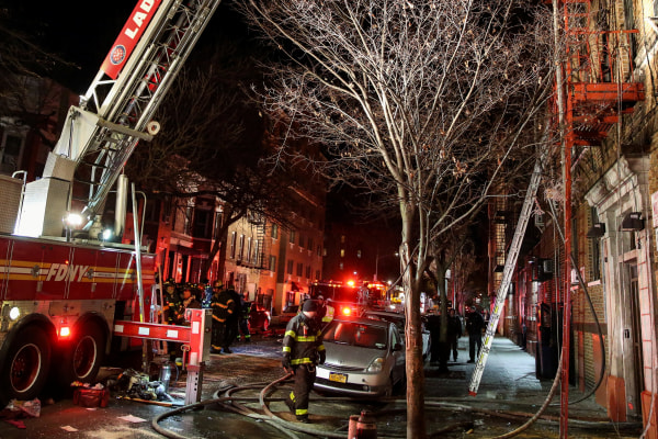 Image: Fire Department of New York (FDNY) personnel work on the scene of an apartment fire in New York