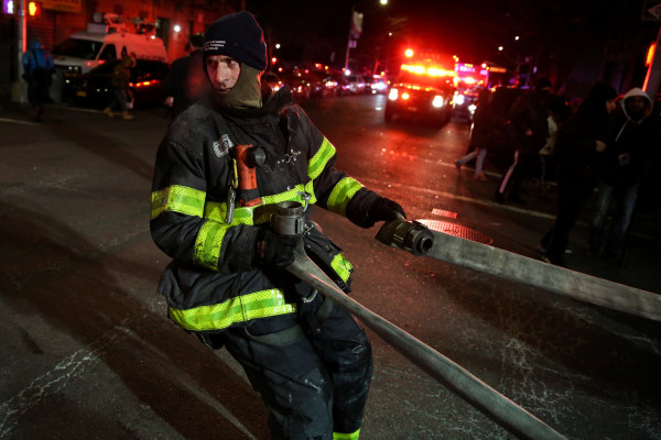 Image: FDNY personnel work on the scene of an apartment fire in New York