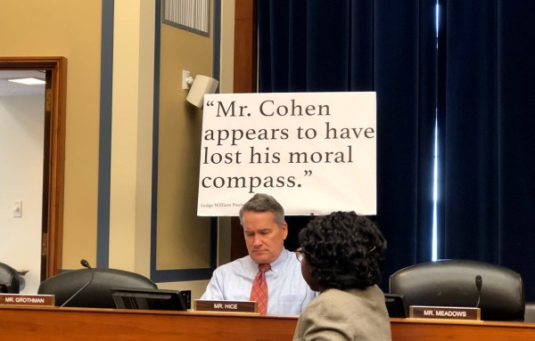 Image: In the hearing room, Republicans put up posters with quotes about Michael Cohen.